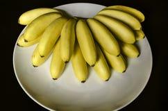 Plato blanco con un manojo en abanico de pequeños plátanos maduros sin pelar Foto de archivo