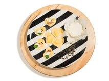 Plato blanco y negro con los raviolis hechos a mano en la forma del corazón, del queso abierto y cerrado, fresco y de algunos gra Imagenes de archivo