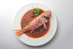Plato con el tomate y el perejil de los pescados del salmonete foto de archivo