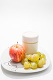 Plato con el yogur, la manzana y las uvas Foto de archivo libre de regalías