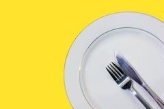 Plato con la bifurcación y cuchillo con el fondo amarillo Fotografía de archivo libre de regalías
