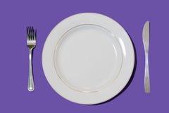 Plato con la bifurcación y cuchillo con el fondo púrpura foto de archivo