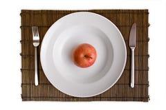 Plato con la manzana en la tarjeta de bambú aislada en blanco Fotos de archivo