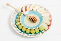 Plato con la miel, fruta en el fondo blanco NY judío, Rosh Hashanah Foco selectivo, pequeña profundidad del campo, lensbaby Foto de archivo libre de regalías