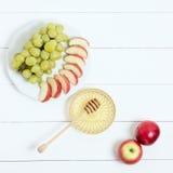 Plato con la miel, la fruta y las manzanas en el fondo de madera blanco Año Nuevo judío, Rosh Hashanah, visión superior Fotografía de archivo libre de regalías
