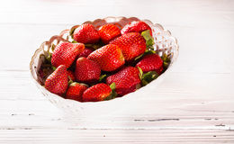 Plato con las bayas rojas de la fresa en los tableros blancos Foto de archivo