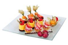 Plato con las mini tortas de chocolate crema y bayas fotografía de archivo libre de regalías