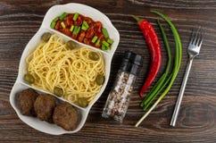 Plato con las pastas, la chuleta, las habas, la cebolla verde y las aceitunas, condimento, pimienta de chile, bifurcación en la t foto de archivo libre de regalías