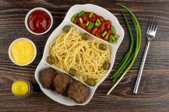 Plato con las pastas, la chuleta, las habas, la cebolla verde y las aceitunas, mayonesa, salsa de tomate, pimienta, bifurcación e fotografía de archivo libre de regalías