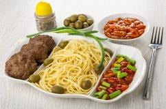 Plato con los espaguetis, la chuleta, las habas, la cebolla y las aceitunas, coctelera de la pimienta, cuencos con las habas, ace foto de archivo