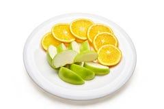 Plato con los limones y las manzanas cortados imagen de archivo