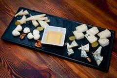 Plato con los quesos clasificados miel y uvas foto de archivo