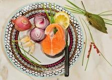 Plato con los salmones frescos, las cebollas, el ajo, el limón, las cebolletas y la pimienta rosada en una tabla de mármol Imagen de archivo libre de regalías