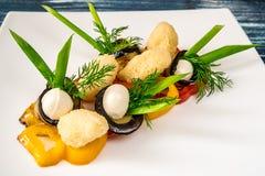 Plato con los tomates, el queso de la mozzarella, la albahaca, el espárrago y balsámico con la salsa del Pesto Fotografía de archivo