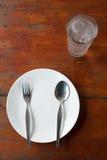 Plato, cuchara y bifurcación en blanco Fotos de archivo