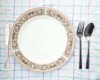 Plato, cuchara y bifurcación en la tabla Fotografía de archivo libre de regalías