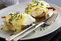 Plato de Benedicto de los huevos que consiste en los huevos escalfados y el jamón cortado en los molletes tostados Fotos de archivo libres de regalías