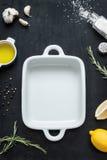 Plato de cerámica blanco vacío de la asación con aceite de oliva, el limón, la sal, la pimienta, el ajo y el romero alrededor Fotografía de archivo libre de regalías