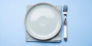Plato de cerámica en colores pastel azul en servilleta con la bifurcación Fotos de archivo