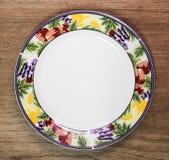 Plato de cerámica hermoso en fondo de madera de la tabla Placa del dise?o en estilo del modelo de la fruta fotografía de archivo libre de regalías