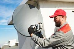 Plato de instalación y que cabe del trabajador del servicio de la antena de satélite para la televisión por cable fotografía de archivo libre de regalías