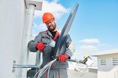 Plato de instalación y que cabe del trabajador del servicio de la antena de satélite para la televisión por cable imagen de archivo