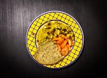 Plato de la comida en fondo de madera negro Cuscús, tomate, cacahuetes, pasas, pan Placa azul amarilla Visión superior imagen de archivo