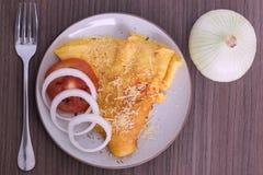 Plato de la tortilla con el queso parmesano, una bifurcación y una cebolla fotos de archivo