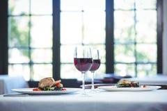 Plato de los espaguetis de la tinta del calamar con la albahaca para dos con los vidrios de vino rojo Fotografía de archivo libre de regalías