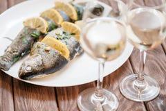 Plato de pescados con los limones en una placa blanca imágenes de archivo libres de regalías