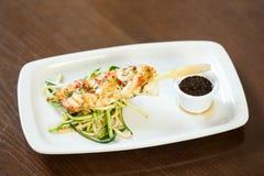 Plato de pescados inspirado asiático con los tallarines y las verduras de la sopa juliana imagen de archivo