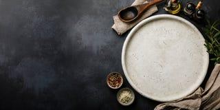 Plato de piedra redondo para cocinar la pizza y las especias en el espacio superficial de la copia del contexto concreto oscuro foto de archivo