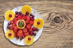 Plato de rebanadas de la naranja y de las fresas con las cerezas en la tabla de madera anudada vieja Imagen de archivo