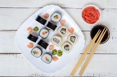 Plato del este tradicional - rollos de sushi con los salmones y el camarón en una placa blanca Imagen de archivo libre de regalías