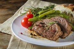 Plato del filete asado a la parrilla del cordero con las habas verdes, los tomates y el pan Fotografía de archivo