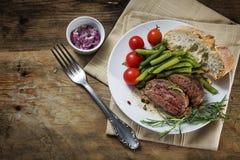Plato del filete asado a la parrilla del cordero del romero con las habas verdes, tomates, Fotografía de archivo libre de regalías