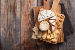 Plato del queso de la prueba en una placa de madera Comida para el vino y romántico, charcutería del queso en una tabla rústica d imagenes de archivo