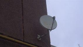 Plato del receptor de satélite en la pared con un cielo nublado y una nube detrás metrajes