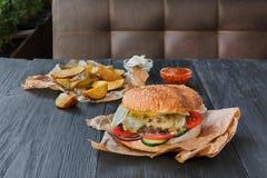 Plato del restaurante de los alimentos de preparación rápida Cuñas de la hamburguesa y de las fritadas foto de archivo
