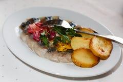 Plato del restaurante - patatas cocidas con los anillos y los arenques de cebolla en una placa blanca fotografía de archivo libre de regalías