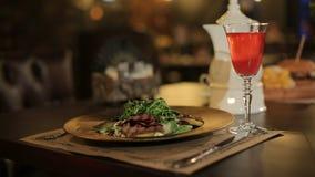 Plato en el restaurante en la tabla y un vidrio de la bebida roja metrajes