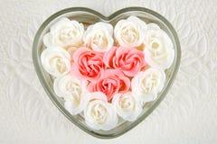 Plato en forma de corazón llenado de las rosas de marfil y rosadas Fotografía de archivo