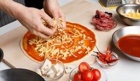 Plato italiano Cocinero que a?ade el queso rallado a la pizza fotos de archivo