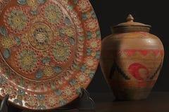 Plato ornamental grabado al lado de un buque de cerámica Fotos de archivo libres de regalías