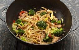 Plato picante de tallarines con la carne y el bróculi en freír el cacerola-wok, en vieja superficie imagen de archivo