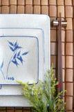 Plato, placa y palillo japoneses en la estera de bambú Fotos de archivo