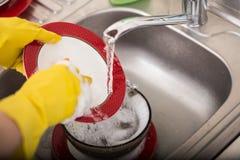 Plato que se lava de la esponja del fregadero de cocina del dishware de la limpieza Ciérrese para arriba de manos femeninas en la Imagenes de archivo