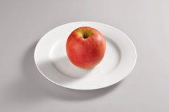 Plato redondo con una manzana roja Foto de archivo libre de regalías