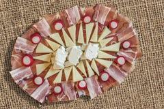 Plato sabroso Meze del aperitivo adornado con los bulbos rojos del rábano fijados en el contexto grueso del Grunge de la lona del Imagen de archivo