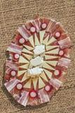 Plato sabroso Meze del aperitivo adornado con los bulbos rojos del rábano fijados en el contexto grueso del Grunge de la lona del Foto de archivo libre de regalías